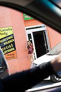 Woman taking a cell phone break outside of a shop. Rawa Mazowiecka Central Poland
