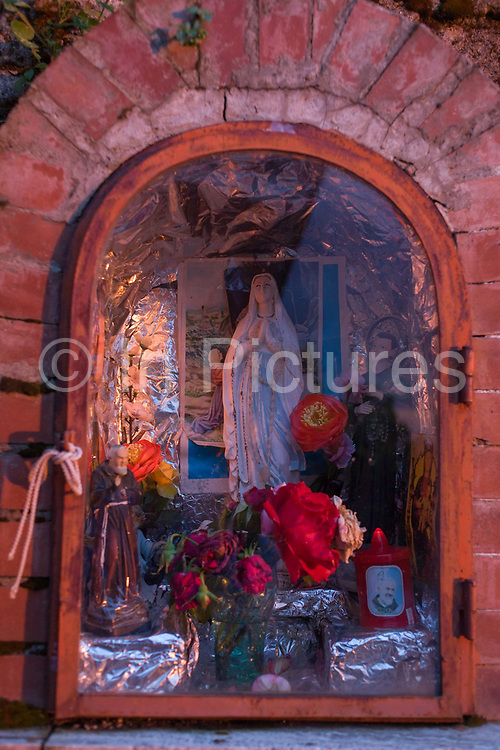"""Religious edicola (aedicula votiva) shrine dedicated to the Madonna, Naples, Somma-Vesuviana, on the slopes of Vesuvius volcano, Italy. The local population is 4m and is the 9th-most populous urban area in the European Union. The De Simons family have owned this land for generations and would choose to stay if the volcano erupts again. """"I was born here, I grew up here, I will die here, I've never been afraid here,"""" says Baldassare. But Giuseppe Mastrolorenzo at the Vesuvius Volcano Observatory in Naples adds, """"There would be no modern precedent for an evacuation of this magnitude .. This is why Vesuvius is the most dangerous volcano in the world."""" From the chapter entitled 'Under the Volcano' and from the book 'Risk Wise: Nine Everyday Adventures' by Polly Morland (Allianz, The School of Life, Profile Books, 2015)."""