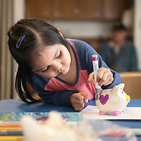 Kara Henderson, 5, decorating a piggy bank at the children's branch of the Octavia Fellin Public Library, Wednesday, Jan. 30.