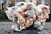 Nederland, Nijmegen, 28-5-2019In een straat met veel studentenhuizen hangen zakken gevuld met plastic afval klaar om door de reinigingsdienst opgehaald te worden. FOTO: FLIP FRANSSEN