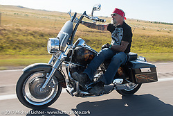Reed Holmes riding south on highway 79 on the Run to the Line for lunch and biker vs Cowboy rodeo games at the Spur Creek Ranch in Newell during the annual Sturgis Black Hills Motorcycle Rally. SD, USA. Wednesday August 9, 2017. Photography ©2017 Michael Lichter.