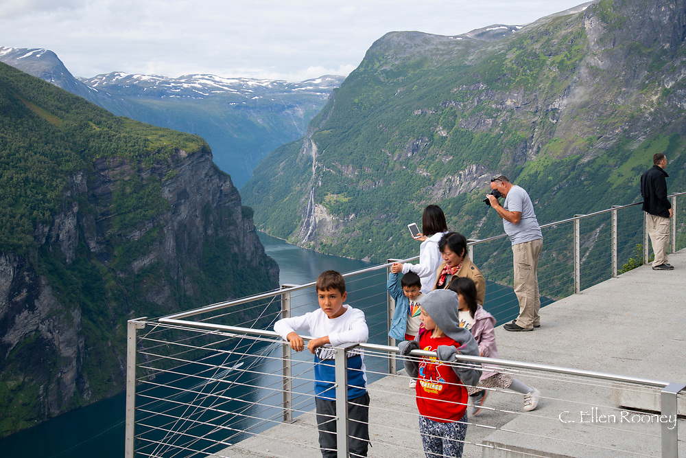 Tourists on a platform overlooking the dramatic scenery around Geiranger Fjord.  Vestlandet, Norway