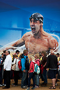 London 2012 Olympic Park in Stratford, East London. Crowds of people queue to get into the London 2012 Megastore to go shopping for related merchandise. Olympic star Michael Phelps adorns the building in a large scale illustration.