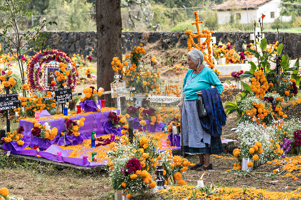 An elderly Purepecha indigenous woman walks through the cemetery decorated with marigold flowers during the Day of the Dead festival November 2, 2017 in Ihuatzio, Michoacan, Mexico.  The festival has been celebrated since the Aztec empire celebrates ancestors and deceased loved ones.