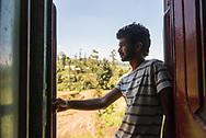 A man enjoys the fresh air at an open door on a train traveling toward Ella, Sri Lanka.