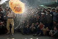 November 1983, Kunming, Yunnan, China --- Crowd Watches Flame Swallower in Kunming Street --- Image by © Owen Franken/CORBIS