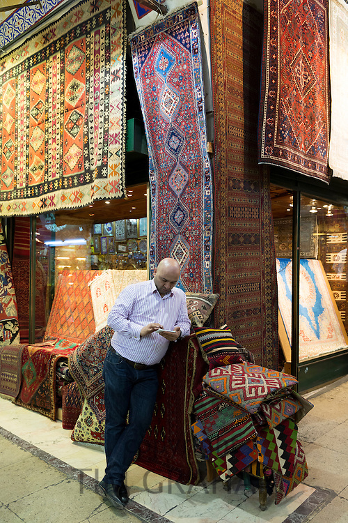Shopkeeper using smartphone at Turkish carpet rug shop in The Grand Bazaar, Kapalicarsi, great market, Beyazi, Istanbul, Turkey
