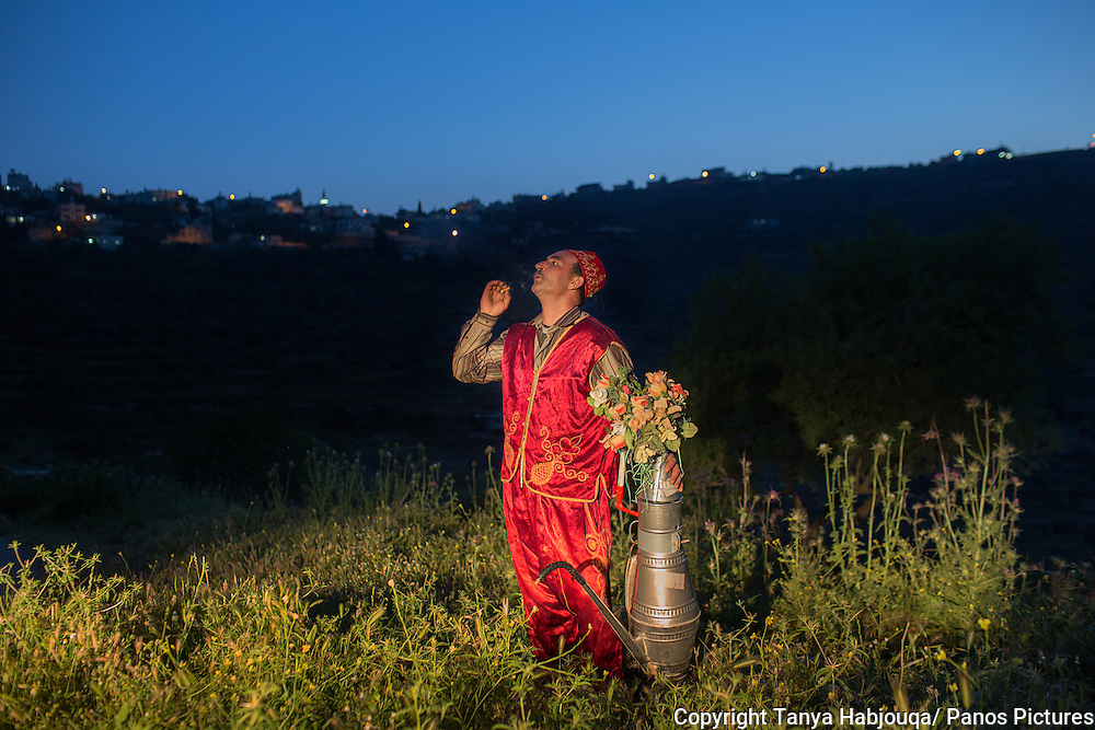 A coffee seller in traditional dress takes a break for a smoke, in Abwein on the West Bank.