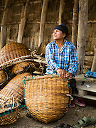 10 FEBRUARY 2016 - BAN LAEM, PHETCHABURI, THAILAND: A woman repairs the baskets used by salt field workers in Phetchaburi province, Thailand. The salt harvest in Thailand usually starts in February and continues through May. Salt is harvested in many of the provinces along the coast, but the salt fields in Phetchaburi province are considered the most productive. The salt fields are flooded with sea water, which evaporates off leaving salt behind. Salt production relies on dry weather and producers are hoping the current drought will mean a longer harvest season for them.      PHOTO BY JACK KURTZ