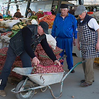 TIMISOARA, ROMANIA - APRIL 21:  Three market sellers load a wheel barrow with potatoes at a daily market on April 21, 2013 in Timisoara, Romania.  Romania has abandoned a target deadline of 2015 to switch to the single European currency and will now submit to the European Commission a programme on progress towards the adoption of the Euro, which for the first time will not have a target date. (Photo by Marco Secchi/Getty Images)