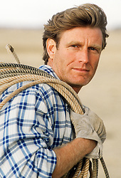 Rugged good looking man with rope over his shoulder