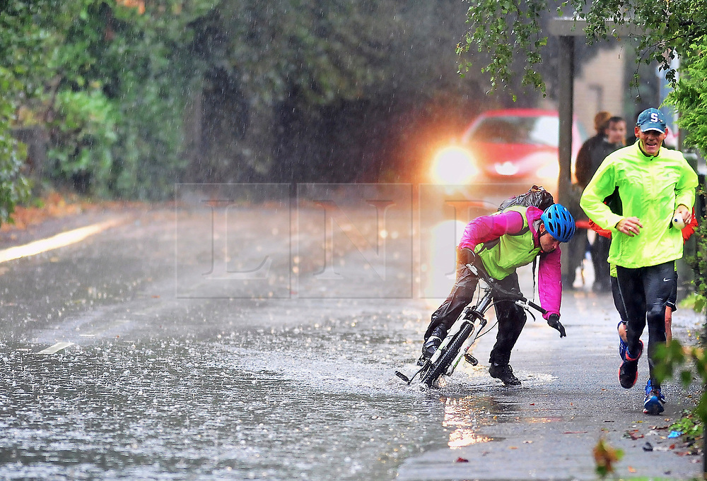 © Licensed to London News Pictures. 23/09/2018<br /> St Mary Cray, UK.<br /> A cyclists is forced to dismount due to surface water as Heavy rain in the South East causing roads to flood.<br /> Photo credit: Grant Falvey/LNP