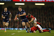 Huw Jones of Scotland © breaks past a tackle from Ken Owens and Hadleigh Parkes of Wales  in the 1st half. Wales v Scotland, NatWest 6 nations 2018 championship match at the Principality Stadium in Cardiff , South Wales on Saturday 3rd February 2018.<br /> pic by Andrew Orchard, Andrew Orchard sports photography