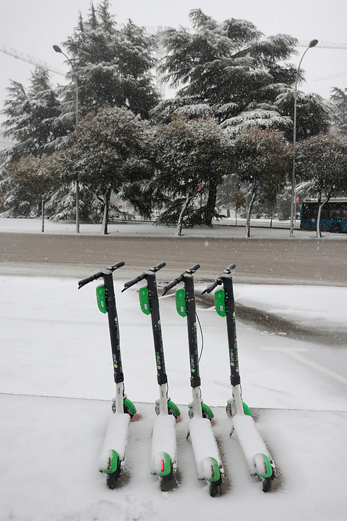 MADRID, SPAIN - JANUARY 8: Sharing-scooters stand on the street under a heavy snowfall at Cuzco Square as storm Filomena hits the city on January 8, 2021, in Madrid, Spain.