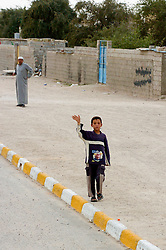 A Young Iraqi boy waves as a British Army patrol of Royal Dragoon Guards passes through Umm Qasr town Southern Iraq, while on Op-Telic in March 2005