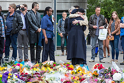 © Licensed to London News Pictures. 05/06/2017. London, UK. Two people share a hug in front of flowers left at London Bridge for those that lost their lives in the terrorist attack that took place on Saturday 3 June 2017. Three attackers drove a van at pedestrians before stabbing a number of people in nearby bars. Photo credit: Rob Pinney/LNP