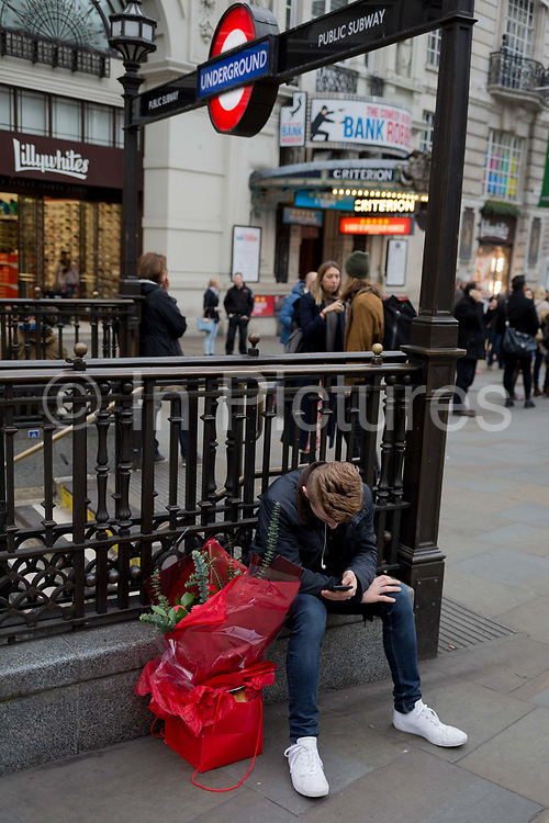 A young man with a bouquet of red roses awaits his girlfriend in Piccadilly Circus, on 15th February 2017, in London borough of Westminster, United Kingdom.