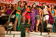 Young women are standing on stage while performing at one of the regular night dance shows being set up during the yearly Sonepur Mela, Asia's largest cattle market, in Bihar, India.