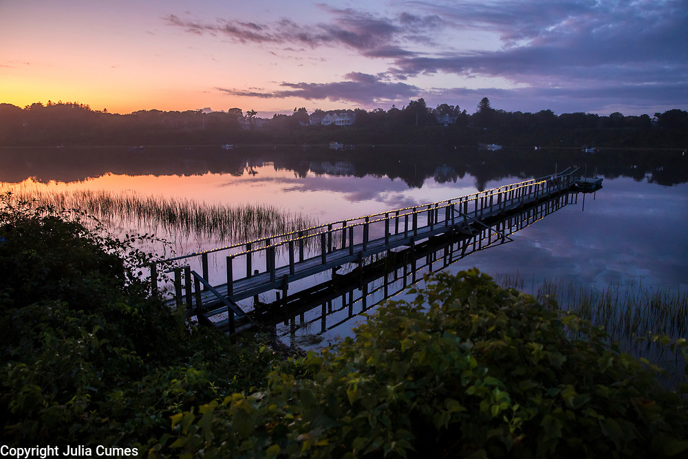 The sun sets over a dock on Mill Pond in Chatham, MA.