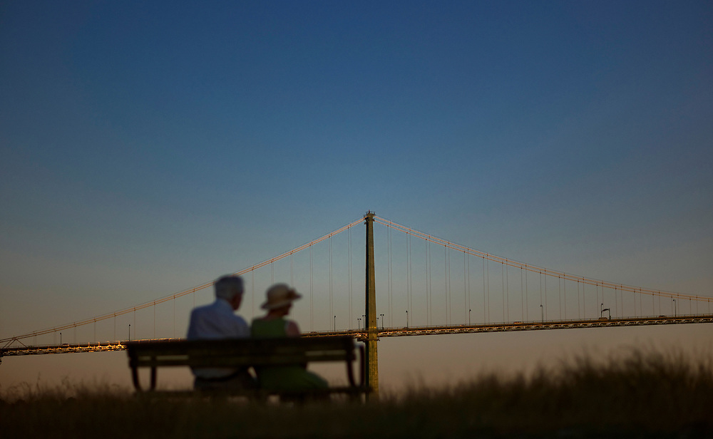 The Lions Gate Bridge and an elderly couple on a park bench at dusk in West Vancouver, BC. (2014)