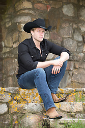 hot cowboy sitting on a stone porch