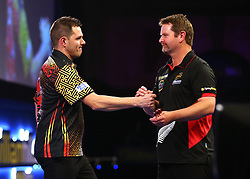 Toni Alcinas and Craig Ross shake hands at the end of the match during day three of the William Hill World Darts Championships at Alexandra Palace, London.