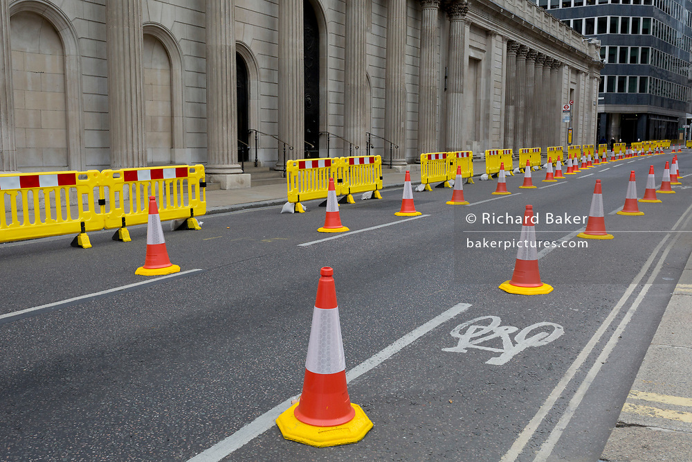 As the UK's Conornavirus pandemic lockdown continues, but with travel restrictions and social distancing rules starting to ease after three months of closures and isolation, yellow barriers and social distance cones have narrowed the road in favour of wider pedestrian pavements outside the Bank of England on a deserted Threadneedle Street, on 9th June 2020, in London, England.