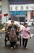 A couple pull a cart they use to collect garbage, such as plastics and paper that can be recycled to earn an income in Luzhou, China.