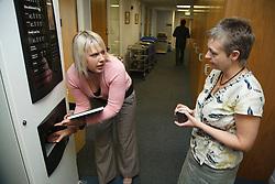 Women in office corridor on coffee break.