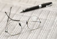 still life of newspaper stocks and shares page with eyeglasses and fountain pen.