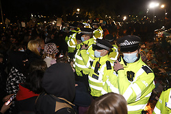 © Licensed to London News Pictures. 13/03/2021. London, UK. Police attempt to break up a vigil for Sarah Everard at the bandstand on Clapham Common. Metropiltan Police officer Wayne Couzens has been charged with the kidnap and murder of Sarah Everard, who went missing as she walked across Clapham Common in south London. The 33-year-old's body was found in Kent just over a week later. Photo credit: Peter Macdiarmid/LNP