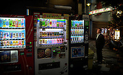 A middle-aged Japanese man confronted by an endless array of choices in vending machines in Tokyo's Golden Gai.