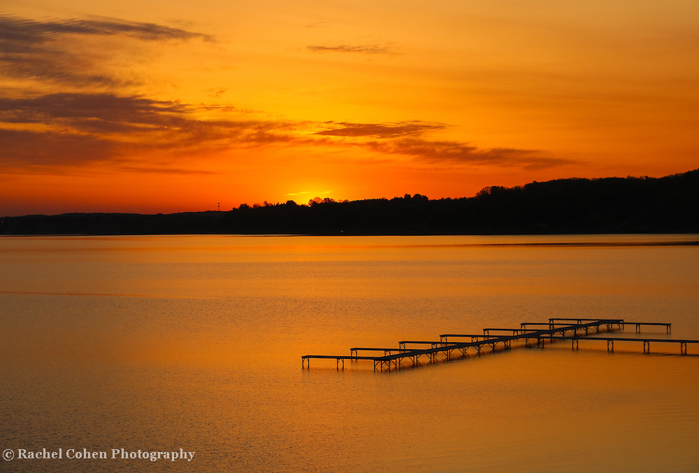 """""""The Dawning""""<br /> <br /> Enjoy a beautiful golden sunrise on Grand Traverse Bay in Traverse City, Michigan from Grand Beach with the shoreline and boat docks in silhouette!"""