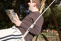 Young man with autism on swing in garden. Cleared for Mental Health issues.
