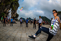 Vietnamese playing a game of Chinese hacky sack (jianzi) with a badminton shuttlecock on Ti top Island. Halong Bay, North Vietnam. The bay features 3,000  limestone and dolomite karsts and islets in various shapes and sizes sprinkled over 1,500 square kilometers. It offers a wonderland of karst topography. It is a UNESCO World Heritage Site.