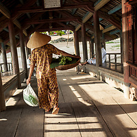 A woman crosses the Thanh Toan bridge on her way to the morning vegetable market in Thanh Toan village outside of Hue, Vietnam.