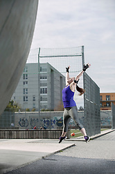 Young woman jumping in mid-air, Bavaria, Germany