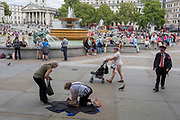 A tired lady visitor to London struggles to her feet on the pavement in Trafalgar Square, on 15th August 2017, in London, England.