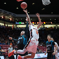 """Gallup Bengals Issac Bustinza (12) tries for a layup as Del Norte Knights defender Matt Antonio (21) reaches for the ball during the NMAA State Tournament. The Knights defeated the Bengals 55-49 at """"The Pit"""" in Albuquerque Wednesday evening."""