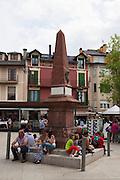 People stting at a monument at Placa de Santa Maria, Puigcerda, Sunday morning, August 2011