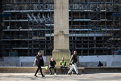 © Licensed to London News Pictures. 26/03/2020. Manchester, UK. People sat at the base of the Cenotaph in St Peter's Square . Manchester City Centre lies nearly empty during a sunny spring afternoon . The British government has imposed a lockdown on all but essential activities and instructed people to reduce social contact as part of quarantine measures to prevent the spread of Coronavirus ( COVID-19 ) . Photo credit: Joel Goodman/LNP