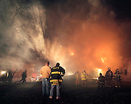 Firefighters work at the rear of a house fire on Conning Road in Scotchtown on the night of Tuesday, March 24, 2009. The fire severely damaged the rear of the structure. tbthr SMOKEY FIRE