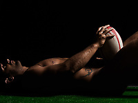 one caucasian sexy naked  man portrait holding rugby ball on studio black background