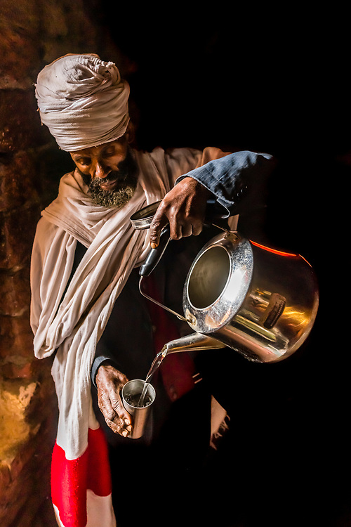 An Ethiopian Orthodox priest pours a cup of holy water in the cave monastery of Neakuto Leab, near Lalibela, northern Ethiopia. The holy water drips from the ceiling of the cave and is collected in a cistern.