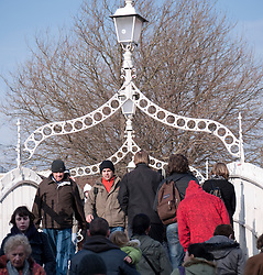 Pedestrians crossing famous Ha'Penny  or Halfpenny Bridge across the River Liffey in Dublin Ireland