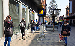 © Licensed to London News Pictures. 27/03/2020. London, UK. Shoppers socially distance while they queue outside a branch of Lidl in Wood Green, north London after UK Government ordered a lockdown to slow the spread of the coronavirus. Photo credit: Dinendra Haria/LNP