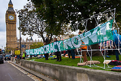 "Parliament Square, London, October 22nd 2014. Protesters from ""Occupy Democracy"" continue their demonstration against what they say is the hijacking of Britain's democracy by capitalism, where big business is allowed to trample people's rights. Having earlier been removed from Parliament square on grounds that they had damaged the threadbare lawn, they continue to demonstrate outside the closed off space. PICTURED: Activists display a banner calling for ""Real Demoicracy Now""."