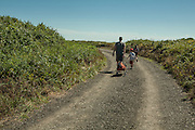 A man and his children walking to the beach, Sakonnet Point, Little Compton, Rhode Island.