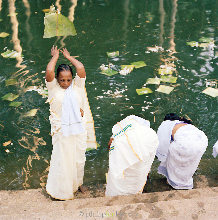 Devotees of Hinduism throw palm leaves into water as part of a ritual, Kerala, India