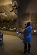 Muslim visitor takes a photo with a smartphone of a pair of giant Assyrian protective spirits - an Ugallu - or great Lion, preceded by what may be a House God from about 700-692BC from the ancient city of Nineveh,